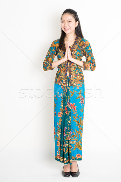 Southeast Asian woman in batik dress greeting Stock photo © szefei