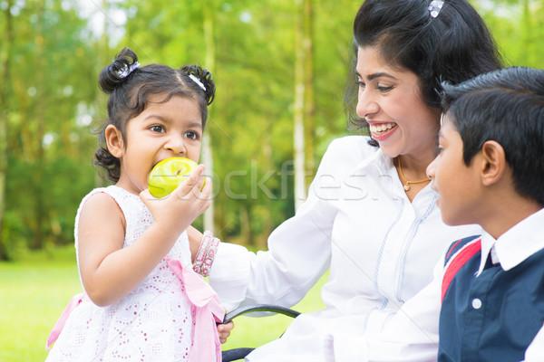 Indian girl eating apple Stock photo © szefei