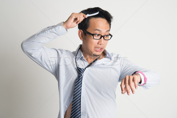 Businessman combing hair in morning in hurry Stock photo © szefei