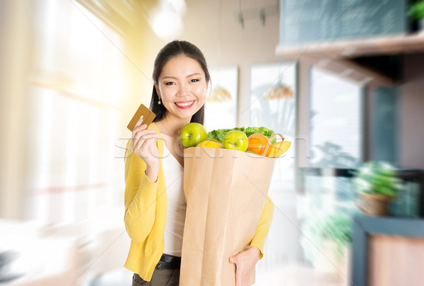 Asian woman holding groceries bag and credit card in market Stock photo © szefei