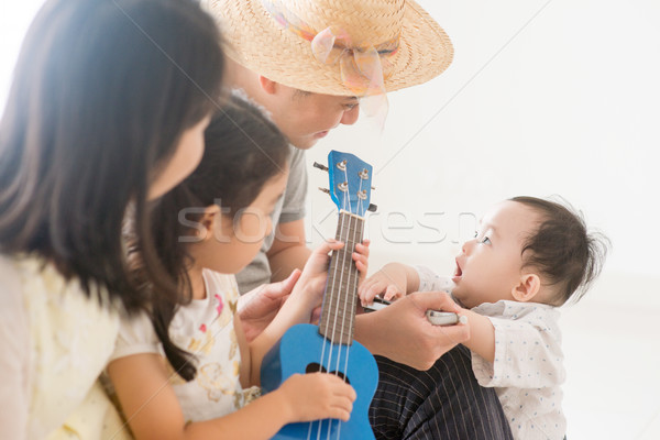 Stock photo: Asian family playing ukulele and harmonica at home