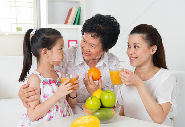 Asian family drinking orange juice.  Stock photo © szefei