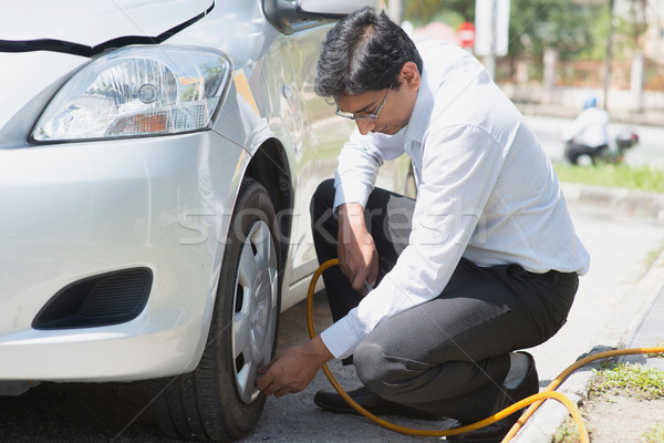 Asian filling air to the car tires. Stock photo © szefei