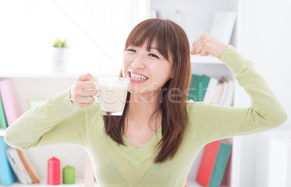 Asian female drinking milk and showing strong arm Stock photo © szefei