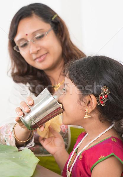 Indian girl drinking water Stock photo © szefei