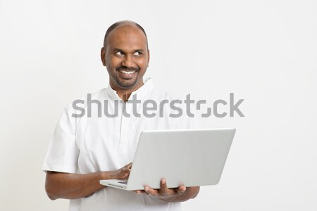 Maduro indio hombre usando la computadora portátil mirando lado Foto stock © szefei
