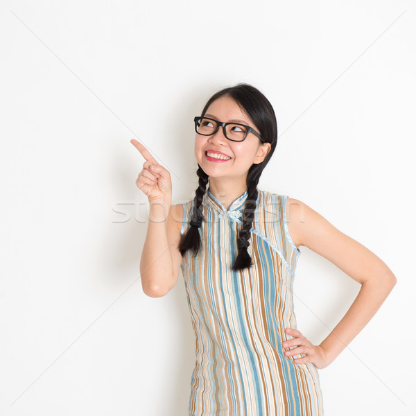 Asian Chinese girl pointing on blank copy space Stock photo © szefei