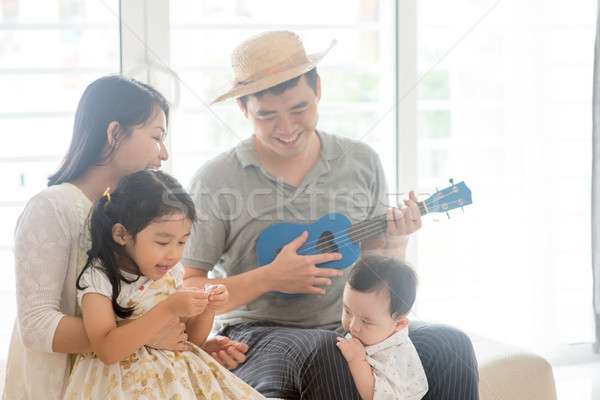 Stock photo: Asian family playing music instrument