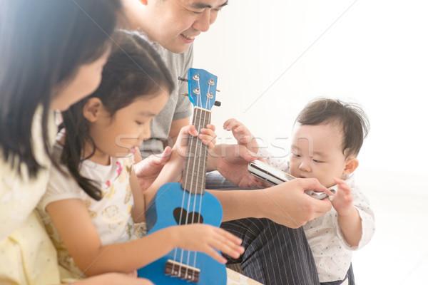 Famiglia giocare armonica home genitori bambini Foto d'archivio © szefei