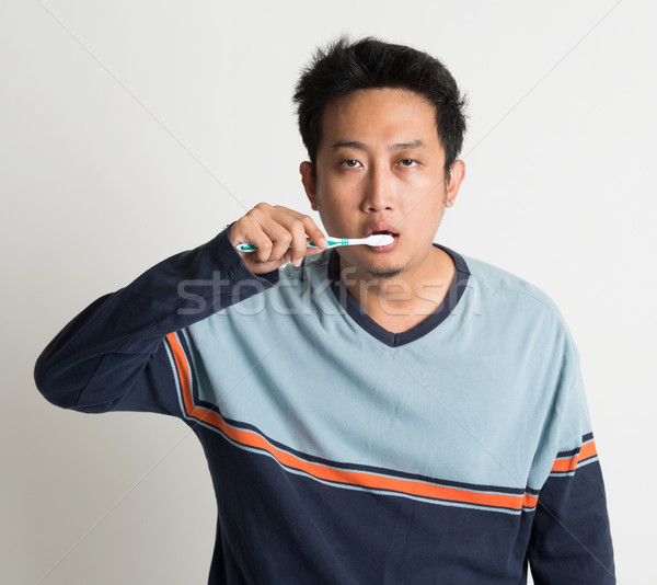 Asian guy brushing teeth  Stock photo © szefei