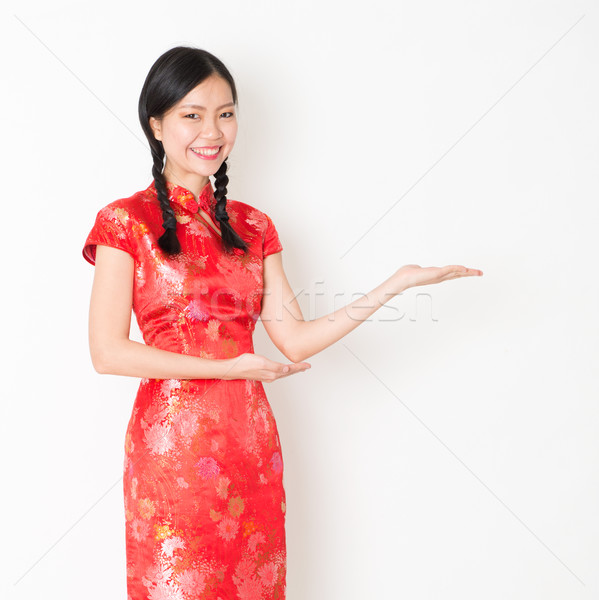 Oriental girl in red qipao hand showing something Stock photo © szefei
