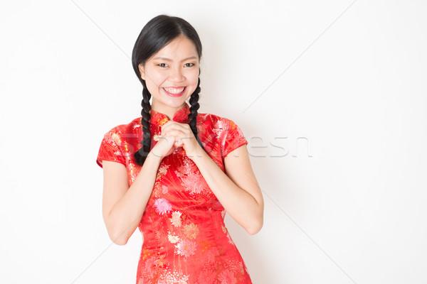 Oriental girl in red qipao greeting Stock photo © szefei