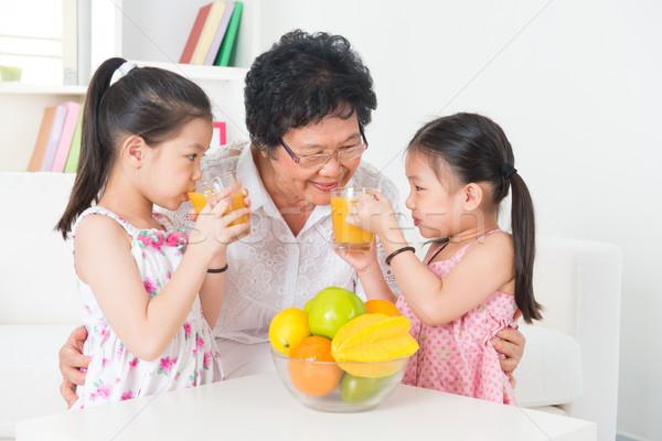 Asian family drinking fresh orange juice Stock photo © szefei