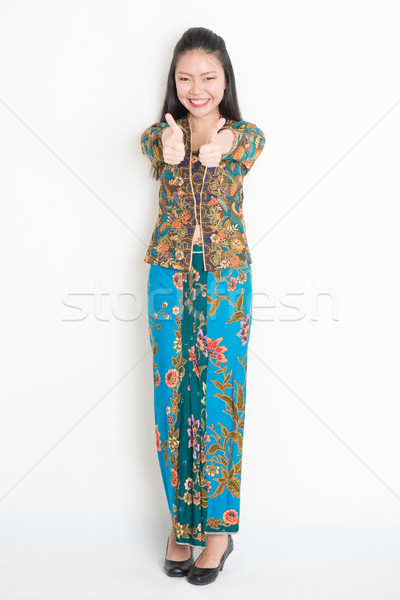 Asian girl giving thumbs up Stock photo © szefei