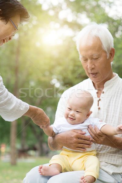 Grandparents and grandson having fun outdoors. Stock photo © szefei