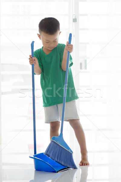 Young boy sweeping floor Stock photo © szefei