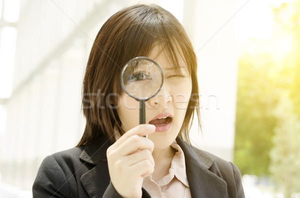 Asian female looking through magnifier glass Stock photo © szefei