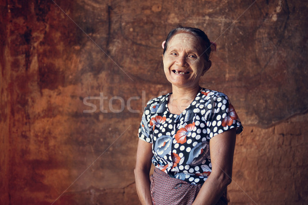 Portrait of traditional old Asian Burmese woman smiling, standing inside a temple, low light, Bagan, Stock photo © szefei