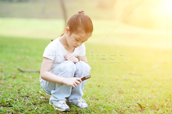 Child exploring nature with magnifier glass at outdoors. Stock photo © szefei