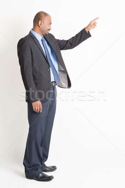 Сток-фото: вид · сбоку · зрелый · индийской · бизнесмен · указывая