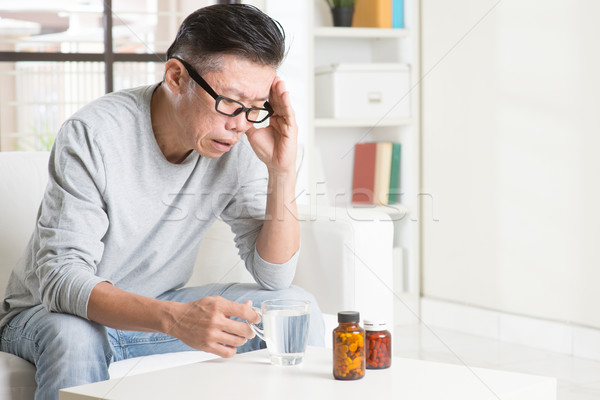 Mature Asian man headache Stock photo © szefei