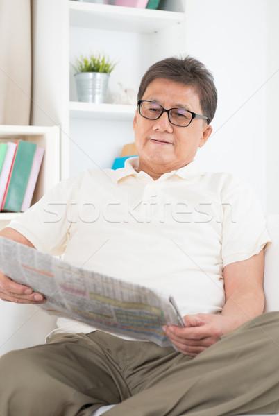 Mature Asian man reading newspaper Stock photo © szefei