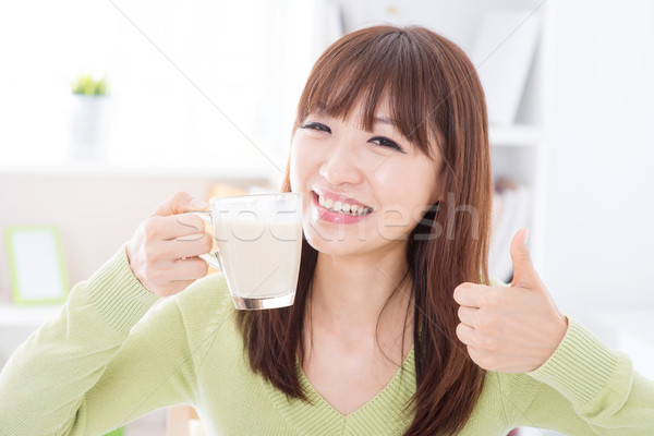 Asian female drinking milk and thumb up Stock photo © szefei