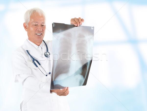 Asian senior doctor checking on x-ray image Stock photo © szefei