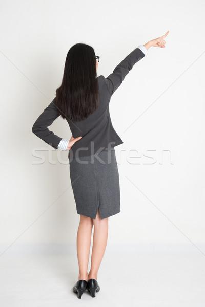 Full length backside Asian business woman pointing Stock photo © szefei