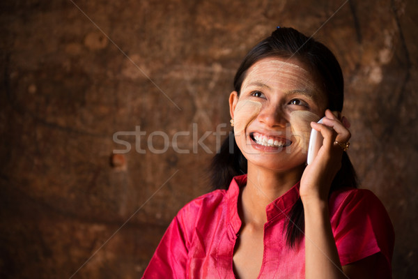 Myanmar girl using smart phone. Stock photo © szefei