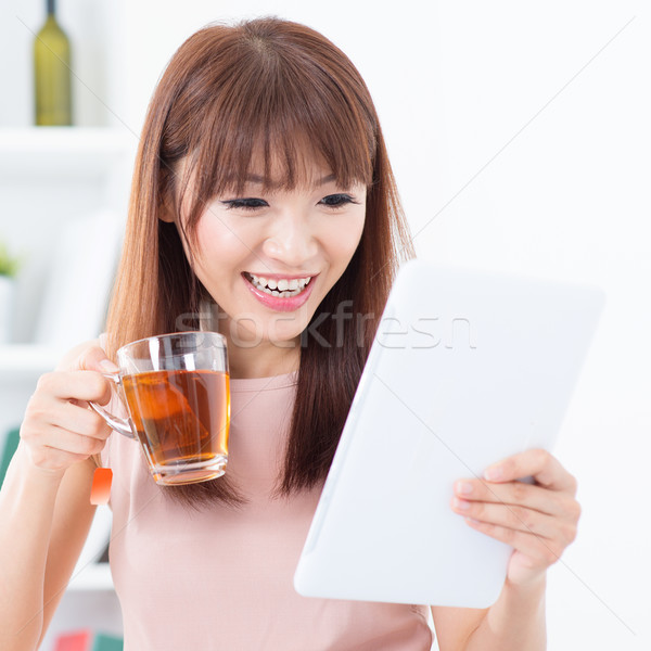 Asian girl drinking tea while using tablet Stock photo © szefei