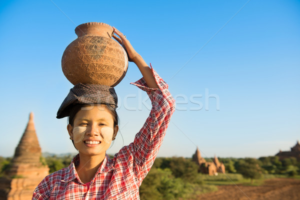 Asian traditional female farmer carrying clay pot on head Stock photo © szefei