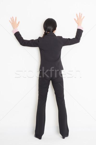 Asian businesswoman banging on wall Stock photo © szefei