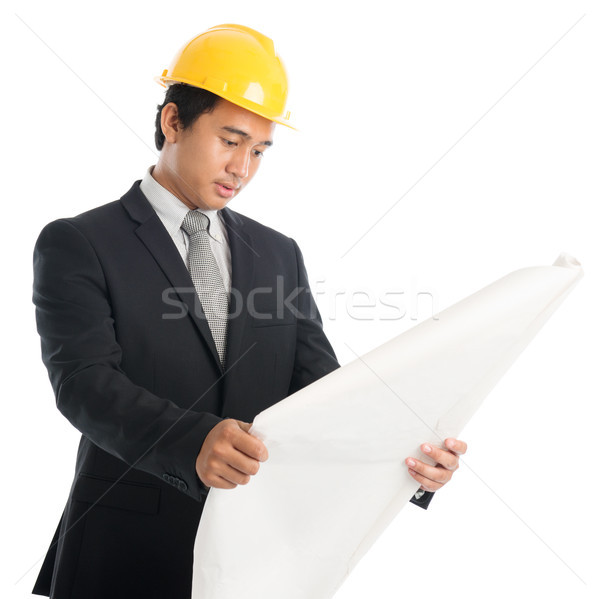Asian guy with safety helmet and blue prints Stock photo © szefei