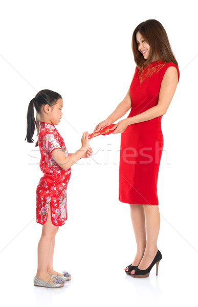 Asian Chinese child receiving monetary gift from parent  Stock photo © szefei