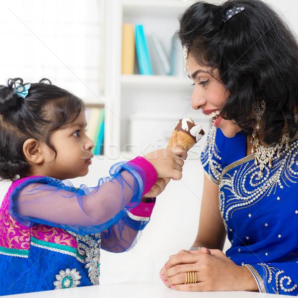 Indian girl feeding her mum ice-cream. Stock photo © szefei
