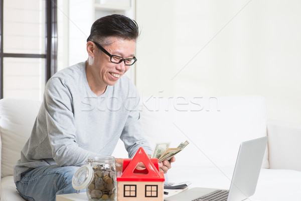 Mature Asian man counting on money Stock photo © szefei