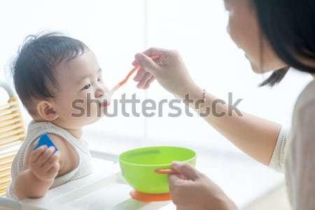 Father feeding baby food. Stock photo © szefei