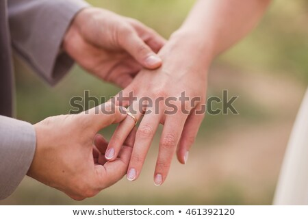 groom putting a wedding diamond ring on bride s finger stock photo © vichie81