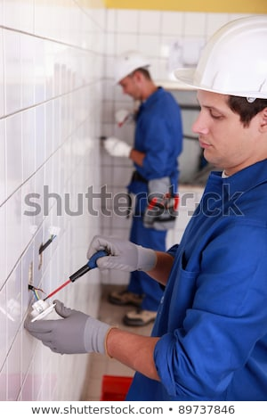 Pair of electricians wiring a white tiled room Stock photo © photography33
