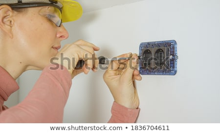 young woman screwing an electrical outlet Stock photo © photography33