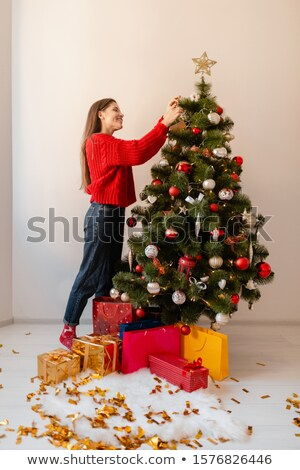 beautiful brunette woman is decorating a christmas tree  Stock photo © juniart