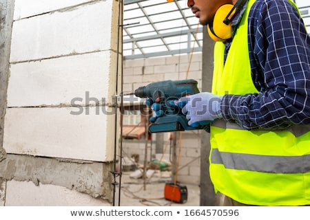 Stok fotoğraf: Man Drilling Hole In Aerating Brick