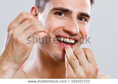 Jeune homme soie dentaire homme beauté portrait dents Photo stock © ambro