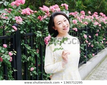 Beautiful woman face among rose petals Stock photo © konradbak
