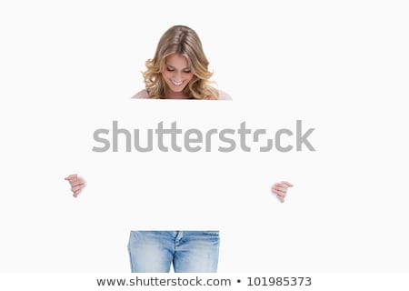 A blonde smiling woman is looking down at a white placard she is holding Stock photo © wavebreak_media