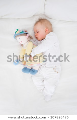 Zdjęcia stock: Baby Sleeping While Holding A Plush Doll In A Bedroom