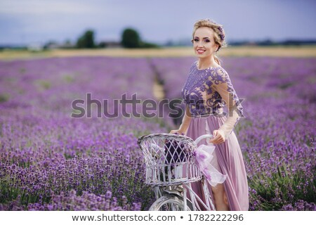 Foto stock: Woman In Purple Dress And Hat With Retro Bicycle In Lavender Field