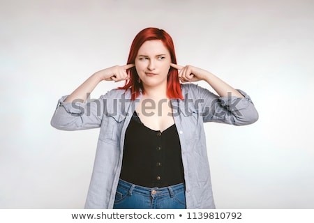 Young woman standing with fingers in her ears Stock photo © bmonteny
