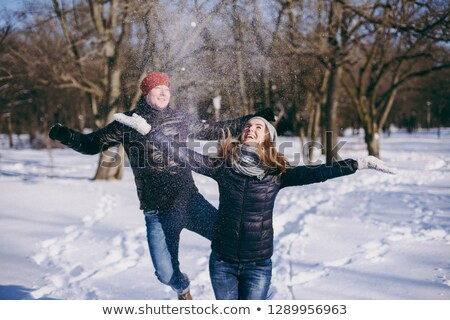 happy young couple jumping in the park outdoors stock photo © deandrobot